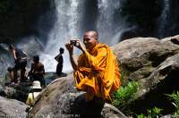 CAMBODIA, Siem Reap. Monk photographing at waterfall, Phnom Kulen.