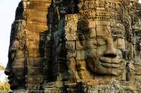 CAMBODIA, Siem Reap. Some of 216 carved stone faces at Bayon temple, built in late 12th century by Buddhist King Jayavarman V11 as centre of his capital of Angkor Thom. Sunset.