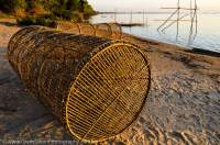 CAMBODIA, Stung Treng. Fish traps on beach beside Mekong River. Sunset.