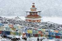 NEPAL, Dolpo. Chortens and mani stone field and Tibetan prayer flags at Shey Gompa (Buddhist), in snow.