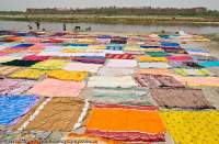INDIA, Uttar Pradesh, Agra. Commercial clothes etc washing beside Yamuna River.