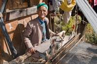 INDIA, Uttaranchal Govind National Park, Jikson. Old man with loom, weaving woollen cloth used for clothes similar to the jacket he is wearing.