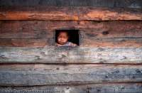 NEPAL, Himalaya, Mt Everest region. Curious child peers from wooden window, Lukla village.