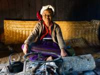 Old Palaung woman sitting at fire site within her traditional-style house, northern Shan Highlands.